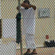 """A detainee covers his face while walking toward his cell in Camp 4 at the Guantanamo Bay detention facility located within the U.S. Naval Station at Guantanamo Bay, Cuba. Camp 4 is a more lenient camp where the most compliant detainees are held in small groups. The U.S. Government is currently holding approximately 340 """"enemy combatants"""" in Guantanamo Bay, Cuba. They were captured during the """"Global War on Terrorism"""" after the attacks on the United States on September 11, 2001. This photo was reviewed by a U.S. Military official before transmission."""