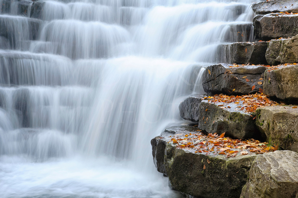 Waterfall flowing over large evenly spaced rock stairs of a dam breast, Johns Mill Run Dam in the fall, Laurel Run State Park, Pennsylvania.