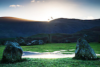 Castlerigg stone circle in Cumbria at sunrise with crows circling above