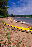 Sea kayaks beached on Stockton Island as a paddler rests in the Apostle Islands National Lakeshore near Bayfield, Wis.