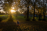 A small child walks through an Autumnal park.
