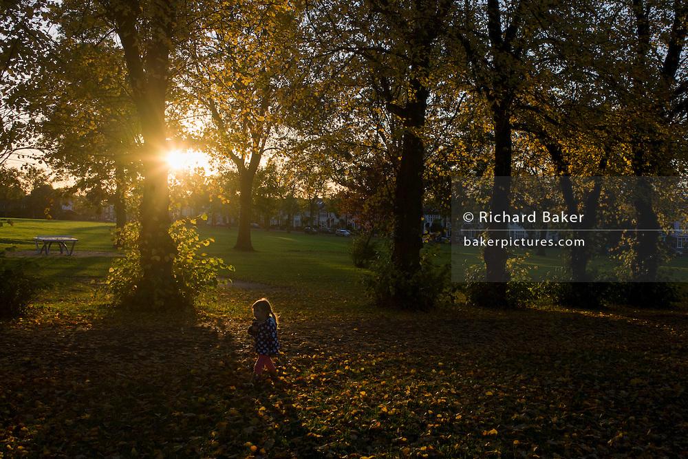 A small child walks through an Autumnal park.