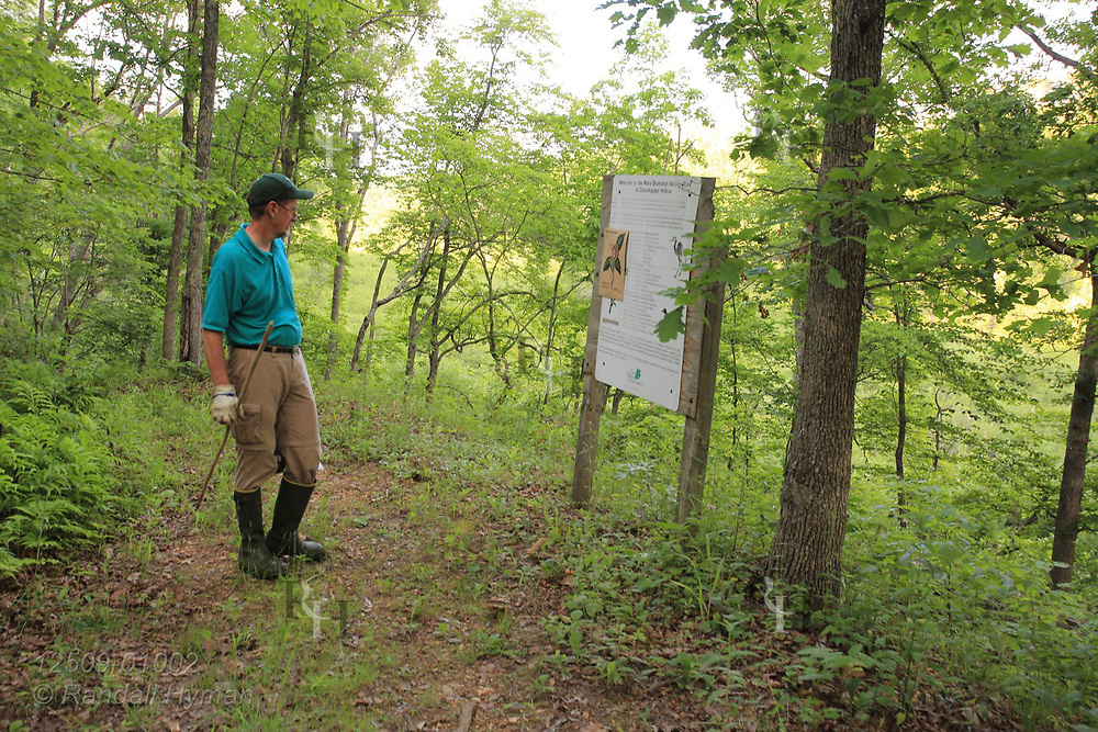 Man reads informational sign describing fauna and flora at Grasshopper Hollow, the largest, most significant fen complex in unglaciated North America; Reynolds, Missouri.