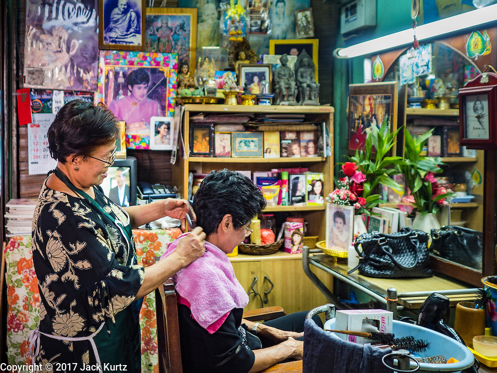 "06 FEBRUARY 2017 - BANGKOK, THAILAND: Woman in a hairdressing shop in what used to be known as Kalabok Market under the Phra Khanong Bridge in the Phra Khanong district of Bangkok. Kalabok is the Thai word for hairdresser and the market was called Kalabok because there were many barbershops and hairdressers under the bridge. In 1985, the city changed the name of the market to ""Singha Market."" There are still about 10 small men's barbershops, most with just one barber, and four women's salons, most with one hairdresser,  under the bridge.      PHOTO BY JACK KURTZ"