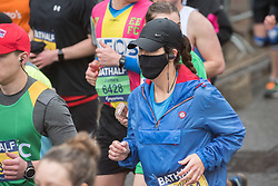 © Licensed to London News Pictures; 15/03/2020; Bath, UK. A woman runs in a face mask at the Bath Half Marathon during the coronavirus crisis. There have been calls to cancel or postpone the event after many other sporting and other events have been cancelled or postponed as cases of infection and deaths due to the virus increase across the UK, and the Government plans to bring in legislation to ban all large public gatherings perhaps as early as next weekend. Organisers of the half marathon say they have taken advice that the risk is low and say that it is too late to cancel the event. Photo credit: Simon Chapman/LNP.