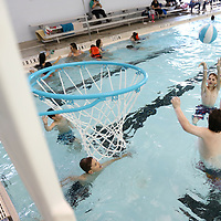Ethan Tice, 12, of Baldwyn, shoots the ball over his friend Landen Michael, 11, of Booneville, as they play a game water basketball at the Tupelo Aquatic Center on Tuesday afternoon. The Aquatic Center has expanded its swim hours for spring break being open from 1-5 everyday.