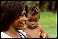 Kanamari woman holding son smiles with brightly painted face in tribal village of Tres Unidos,AM Brazil