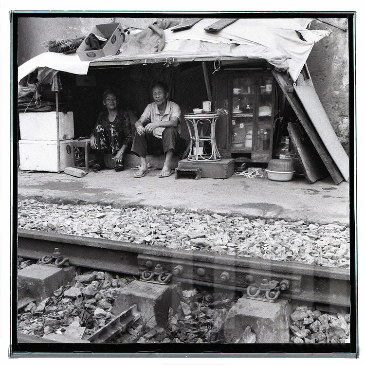 Black and white picture of a couple living in a shanty town along the railway of Hanoi.