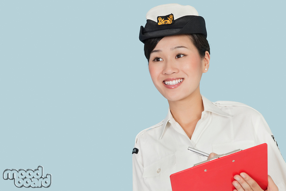Happy female US Navy officer with clipboard smiling over light blue background