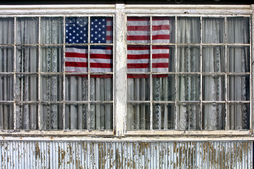 Oct 25, 2001; Huntington Beach, CA, USA; The sharp color contrast of the American Flag shows through the window of an old house on Main Street.  Displaying the Red, White and Blue flag became a patrotic trend in the United States for a few months following the events of 9/11. Mandatory Credit: Photo by Shelly Castellano/ZUMA Press.