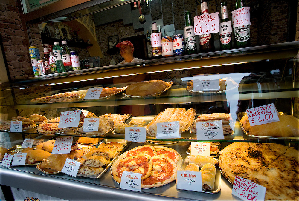 A shopkeeper waits for customers in his sandwich shop in the Spaccanapoli shopping district of Naples.