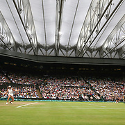 LONDON, ENGLAND - JULY 11:  Johanna Konta of Great Britain in action against Simona Halep of Romania in the Ladies' Singles Quarter Final match under the closed roof on Center Court during the Wimbledon Lawn Tennis Championships at the All England Lawn Tennis and Croquet Club at Wimbledon on July 11, 2017 in London, England. (Photo by Tim Clayton/Corbis via Getty Images)