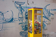 Traditional seaside imagery and contemporary toy dispenser in Barra, Costa Nova, Aveiro, Portugal.
