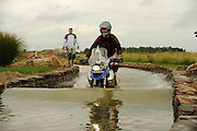 53 year old Bill Dragoo of Norman, Oklahoma traverses a water crossing at the BMW GS Trophy Challenge while a judge observes.