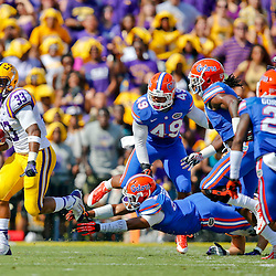 Oct 12, 2013; Baton Rouge, LA, USA; LSU Tigers running back Jeremy Hill (33) escapes a tackle by Florida Gators linebacker Michael Taylor (51) during the first quarter of a game at Tiger Stadium. Mandatory Credit: Derick E. Hingle-USA TODAY Sports
