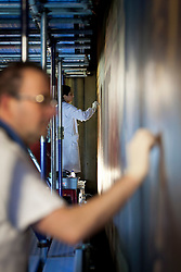 © Licensed to London News Pictures. 03/01/2013. London, UK. Restoration expert Carla Markland (background) and Francesco Rossellini (foreground) work on the the Baroque painted West Wall as part of the renovation works on the Painted Hall at the Old Naval College in Greenwich London today (03/01/12). The restoration, funded by the Heritage Lottery Fund (HLF), is the Painted Hall's 10th since being built in 1742 and is estimated to take around four months. Photo credit: Matt Cetti-Roberts/LNP