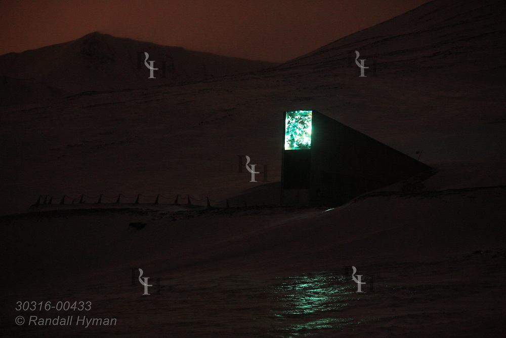 Global Seed Vault glows over snowy hillside in January during the long polar night in Longyearbyen on Spitsbergen island, Svalbard, Norway.
