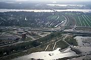 Nederland, Zuid-Holland, Sliedrecht, 08-03-2002; in Z richting, naar rivier Beneden Merwede, met zuiverinsinstallatie (schoorsteen) en een er achter gelegen spaarbekken; spoorlijn Gorinchem - Dordrecht kruist auosnelweg A15; links benededen bedrijventerrein, daar boven nieuwbouwwijk, rechts Polder Papendrecht, rechts beneden:  grond / bagger depot  Betuweroute; knooppunt infrastuctuur stadsgezicht verkeeren vervoer;<br /> <br /> luchtfoto (toeslag), aerial photo (additional fee)<br /> foto /photo Siebe Swart