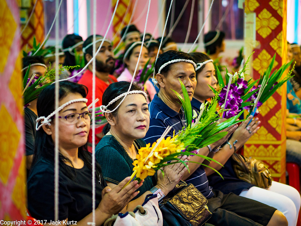 """24 JUNE 2017 - BANG KRUAI, NONTHABURI: People pray during a """"resurrection"""" or rebirthing ceremony at Wat Ta Kien (also spelled Wat Tahkian), a Buddhist temple in the suburbs of Bangkok. The strings around their heads are connected to a web of strings that is supposed to amplify the power of the prayers. People go to the temple to participate in a """"Resurrection Ceremony."""" Thai Buddhists believe that connecting people by strings around their heads, which are connected to a web of strings suspended from the ceiling, amplifies the power of the prayer. Groups of people meet and pray with the temple's Buddhist monks. Then they lie in coffins, the monks pull a pink sheet over them, symbolizing their ritualistic death. The sheet is then pulled back, and people sit up in the coffin, symbolizing their ritualist rebirth. The ceremony is supposed to expunge bad karma and bad luck from a person's life and also get people used to the idea of the inevitability of death. Most times, one person lays in one coffin, but there is family sized coffin that can accommodate up to six people. The temple has been doing the resurrection ceremonies for about nine years.     PHOTO BY JACK KURTZ"""