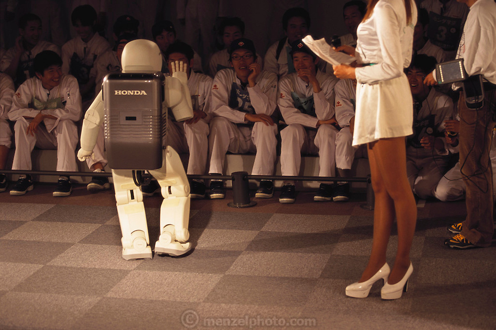 In Suzuka City, Japan, ASIMO, (Advanced Step in Innovative Mobility), a humanoid robot designed by Honda stands with the Suzuka Circuit Queen, and waves to the audience. Honda's walking robot, is child-sized and has more maneuverability than it's predecessor, the Honda P3. Unlike the P3, which couldn't be stopped once it began it's programmed routine, ASIMO can be controlled by either joystick or computer program. Pictured here at Suzuka City (a race track and amusement park), Japan.