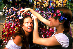 Stock photo of one girl placing flowers in another's hair at the Texas Renaissance Festival in Plantersville Texas