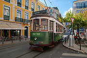 Green tram navigates the crowded narrow streets of Lisbon, Portugal