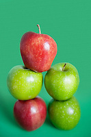 Pile of red and green apples over colored background