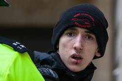 Whitehall, London, April 4th 2015. As PEGIDA UK holds a poorly attended rally on Whitehall, scores of police are called in to contain counter protesters from various London anti-fascist movements. PICTURED: Wearing a hunt saboteurs hat, a young anti-fascist counter-protester stares into the camera as he is arrested after attempting to break through police lines into the PEGIDA rally.