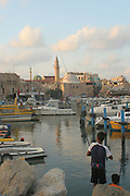 Israel, western Galilee, Acre, The Harbour now a fishing port. The El Bahar Mosque can be seen in the background