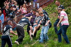 © Licensed to London News Pictures. 25/05/2015. Brockworth, Gloucestershire, UK.  An injured man is carried off the Coopers Hill at the annual traditional Cheese Rolling races, which by custom take place on Bank Holiday Monday.  Participants race down a very steep hill chasing a Double Gloucester Cheese, and injuries sometimes happen. Photo credit : Simon Chapman/LNP