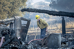 October 29, 2019, Windsor, California, USA: Santa Barbara County Firefighter SHANKAR TILLOTSON, mops up a hot spot of a barn that burned Sunday. Californians are bracing for more howling winds as the region could experience the strongest winds of the season Tuesday night. Tens of thousands of people remain under evacuation. By Tuesday, the Kincade Fire has grown to 75,415 acres, Cal Fire said. (Credit Image: © Erick Madrid/ZUMA Wire)