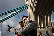 Asian tourists walk beneath one of the steel suspension chains and the south abutment tower, on 14th December 2017, in the City of London, England.