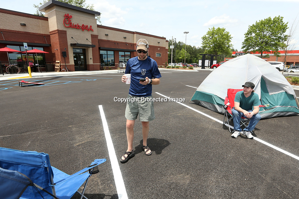 Matthew Nunnelee, of Tupelo, checks his phone and he and Jeremy Hopper, also of Tupelo, camp out in the parking lot of the new Chick-fil-a in Tupelo on Wednesday. Nunnelee arrived at the restaurant at 5:15AM with Hopper arriving at 4:30AM. The restaurant reopens Thursday morning, but the first 100 people in line get free Chick-fil-a for a year.
