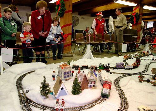 Joan Trame (standing) talks with Zachary George, 3 of Kettering (wearing Thomas the Tank shirt) as they watch the train display during the Polen Farm Christmas Gathering, Saturday, December 25, 2010.  Visitors could watch trains, talk to Santa, sing carols and enjoy the Christmas buffet.