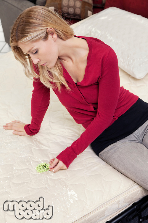 Young woman sitting mattress while looking at price tag