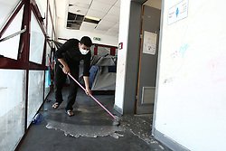 October 5, 2016 - Athens, Greece - A man cleans the floor at the former Athens airport departure hall of Athens, Greece on October 5, 2016.Almost 2,500 migrants and refugees, mainly Afghani, are housed at the former Athens airport site, and to an olympic complex used in the 2004 Olympics. In total 60.736 refugees and other migrants are stranded in Greece. (Credit Image: © Panayiotis Tzamaros/NurPhoto via ZUMA Press)