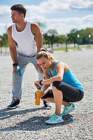 Young couple drinking energy drinks while resting in park
