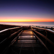 a wooden walkway leads to the beach as the ocean reflects the beautiful and vibrant purple and orange colors of the sky before the sun rises to greet the day in Kiawah, South Carolina