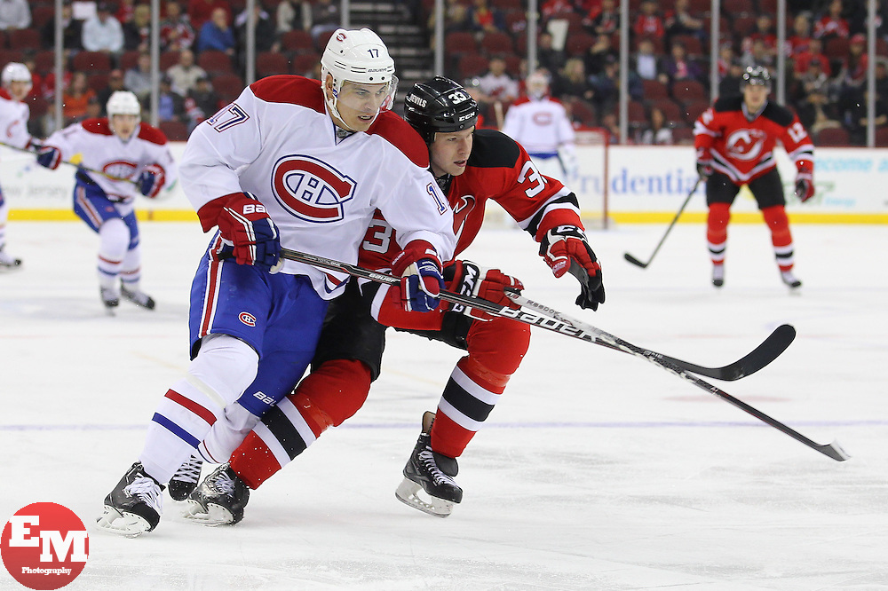 Apr 23, 2013; Newark, NJ, USA; Montreal Canadiens left wing Rene Bourque (17) and New Jersey Devils defensemen Alexander Urbom (33) chase the puck during the first period at the Prudential Center.