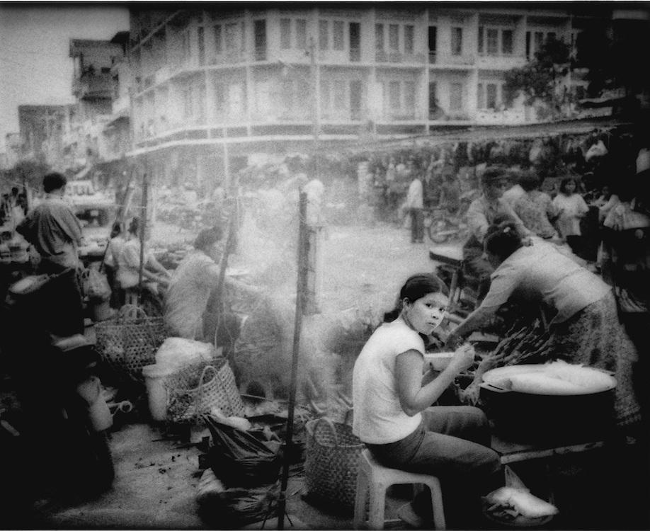Girl having dinner in market, Phnom Penh, Cambodia.