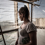 "Tulipa is 22 years old and shares with her boyfriend Pavel, Nadina and Anton a two-room storehouse with a plastic roof close to Vittoria, Sicily, Italy. As the other women, she works twelve hours a day, and earn as little as 25 to 30 euros, less than the male counterpart for the same tasks.  ""I have a daughter who lives in Romania with her grandmother. Bringing the child to the farm is not safe. Life here is not easy, we have to accept really difficult conditions of work. As women it is even worst because we risk always to be sexually harassed. We know that we would deserve more worker rights""."