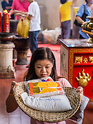 "26 AUGUST 2013 - BANGKOK, THAILAND:     A woman prays before donating rice and staples to the Poh Teck Tung Foundation for Hungry Ghost Month in Bangkok. Poh Teck Tung operates hospitals and schools and provides assistance to the poor in Thailand. The seventh lunar month (August - September in 2013) is when the Chinese community believes that hell's gate will open to allow spirits to roam freely in the human world for a month. Many households and temples will hold prayer ceremonies throughout the month-long Hungry Ghost Festival (Phor Thor) to appease the spirits. During the festival, believers will also worship the Tai Su Yeah (King of Hades) in the form of paper effigies which will be ""sent back"" to hell after the effigies are burnt.   PHOTO BY JACK KURTZ"