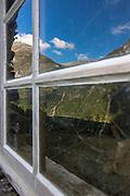 Reflection from a window at Skageflå, Geiranger, Norway, with view to Geirangerfjord   Speilbilde fra et vindu på Skageflå, med utsikt til Geirangerfjord.
