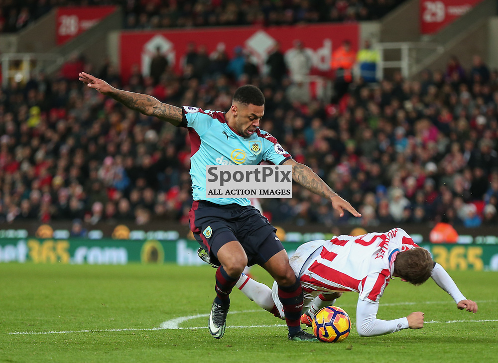 STOKE-ON-TRENT, UNITED KINGDOM 03 DECEMBER 2016: Andre Gray of Burney is challenged by Marc Munesia, who receives a yellow card  during the league game between Stoke City and Burnley at the Britannia Stadium, on December 03, 2016 in Stoke-on-Trent, England. (Photo by Michael Poole)