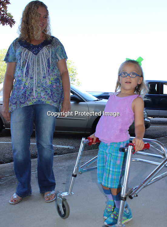 RAY VAN DUSEN/BUY AT PHOTOS.MONROECOUNTYJOURNAL.COM<br /> Amelia Moody heads down a downtown Amory sidewalk with her mother, Heather. Amelia was born with cerebral palsy and is scheduled for a surgery to help her walk in St. Louis. The family has been denied coverage numerous times for the medical procedure.