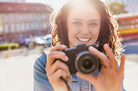 Young attractive woman holding camera and taking photo