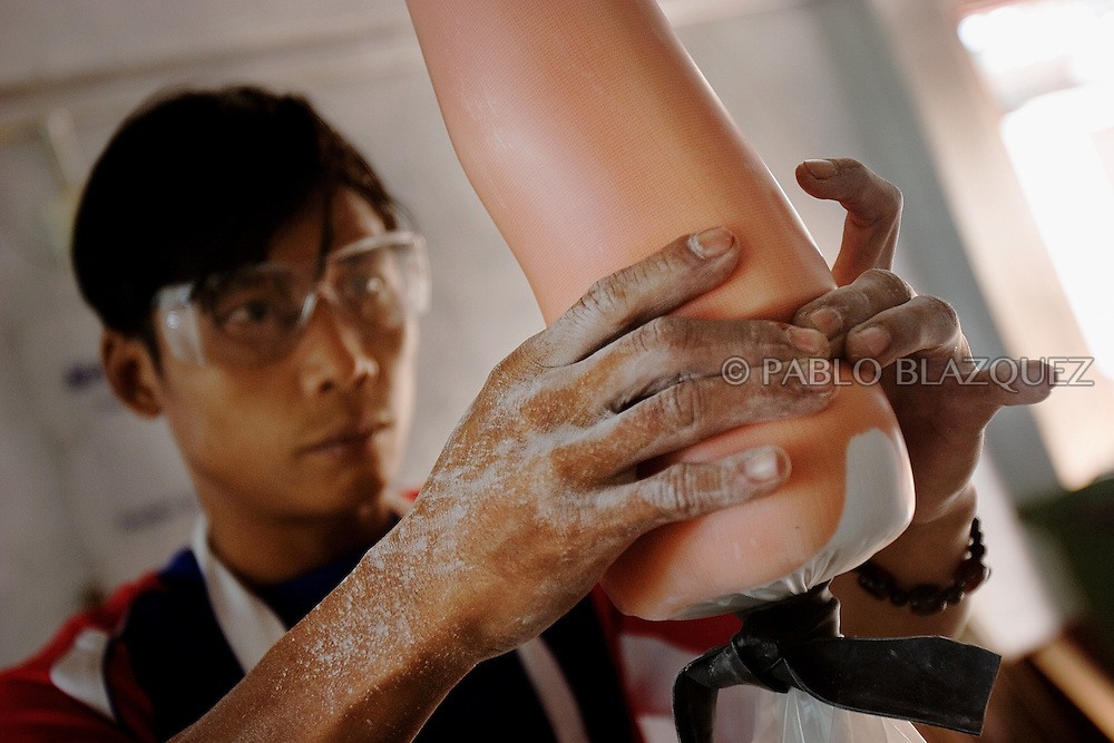 A man manufactures an artificial limb at Mae Tao Clinic's lab, on December 20 of 2006, in Mae Sot area, Thailand. On 2004, the Clinic recorded 17 patients from land-mines. Now they even deliver the protheses to the land-mine victims' villages so they do not need to travel..Many of the people working in the Clinic arrived as patients, but then they learned the skills to treat patient and help in the clinic..The Mae Tao Clinic was founded on 1988 by Dr. Cynthia Maung and gives medical care for migrant and refugees, fleeing Burma, in the Mae Sot area, Thailand..Burma has since 1962 been ruled by dictator Burman Regimes. Pro democrats and minority ethnics have since been object of human rights abuses and armed minority groups has appeared, bringing a state of Civil War..This has forced Burmese people to flee their villages and on their arrival to Thailand many suffer from malnutrition, illnesses and injuries, amputations from land-mines or traumas. The Mae Tao Clinic supported by donors and volunteers provides with free health care and treatment to these people.