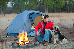 Man in a red jacket sitting bside a campfire with his dog