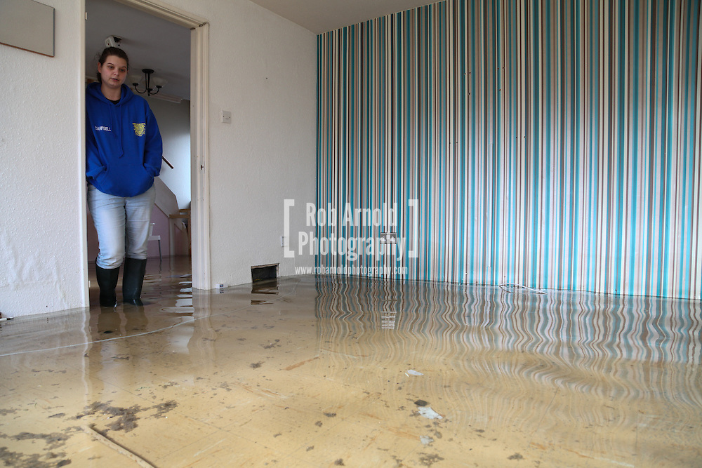 24/02/2014. Basingstoke, Hampshire, UK. Kirsty Campbell (23) looking inside her house on Sperrin Close which she and her family have had to evacuate due to groundwater flooding in the Buckskin area of Basingstoke, Hampshire. The house, a council property operated by Sovereign, was first flooded on 8th February 2014. The council initially told her that they were unable to provide flood support for the area. The area is now being continuously pumped by tankers in an attempt to reduce the volume of flood water. Photo by Rob Arnold
