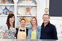 Portrait of mature couple with employees in cake shop